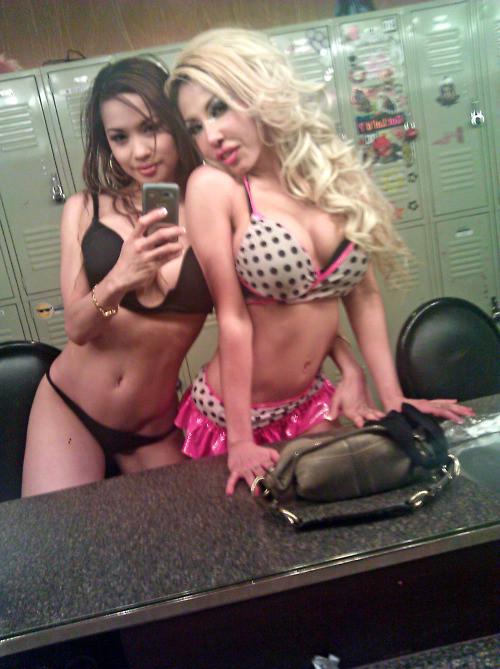 two strippers in underwear taking selfie photo in strip club change room